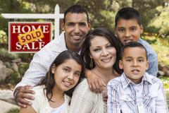 Happy Hispanic Family in Front of Sold Home for Sale Real Estate Sign. - stock photo