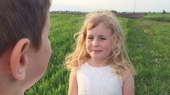 Young girl sincerely looking into the eyes of a young boy on a green spring Stock Footage