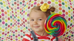 Cute funny girl 3.5 years old licking a big lollipop Stock Footage