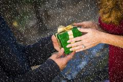 Hands of Man and Woman Exchanging a Wrapped Christmas Gift in the Snow. - stock photo