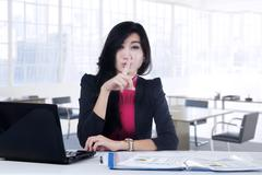 Stock Photo of Young manager showing silent sign