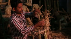 Man shaping a form using straw in workshop in Varanasi. Stock Footage