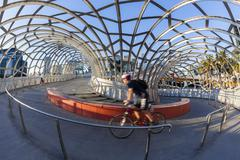 View of cyclist riding along the Webb Bridge in Docklands, Melbourne - stock photo