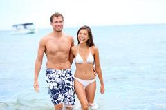 Beach couple in love walking happy in water enjoying summer holidays Stock Photos