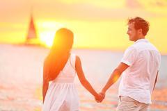 Couple in love happy at romantic beach sunset Stock Photos