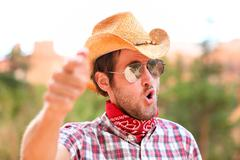 Cowboy man with sunglasses and hat pointing Stock Photos