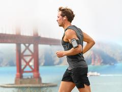 Running man - male runner in San Francisco listening to music on smart phone - stock photo