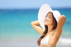 Relaxing beach woman enjoying the summer sun happy - stock photo