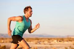 Running man sprinting cross country trail run - stock photo