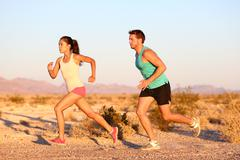 Cross-country trail running people at sunset - Runner couple exercising - stock photo