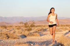 Woman runner running cross country trail run -  Female jogger training outside Kuvituskuvat