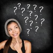 Student thinking with question marks on blackboard - stock photo