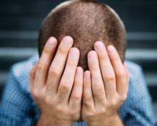 Closeup portrait of despaired young man covering his face with hands - stock photo