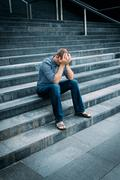 Despaired young man covering his face with hands sitting on stairs Stock Photos