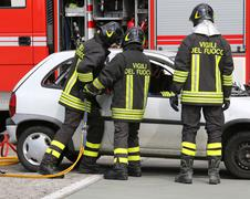 brave firefighters relieve an injured after a road accident - stock photo