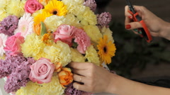 Modern florist puts pale yellow carnations in a bouquet of tulips, lilacs, roses Stock Footage