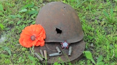 red poppy near the shattered helmet and a medal of the Red Star - stock footage