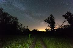 Rut road and Milky Way Galaxy in sky Stock Photos