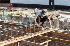 The worker is constructing underground floor of the building - stock photo