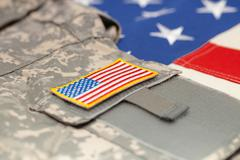 US flag with army uniform over it - studio shot Stock Photos