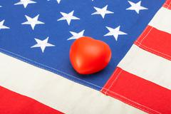 US flag with toy heart over it - studio shot - stock photo