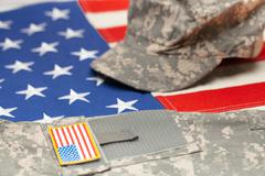 US flag with US military uniform over it - studio shot - stock photo