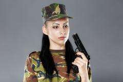 Female soldier in camouflage uniform with weapon isolated on gray background - stock photo