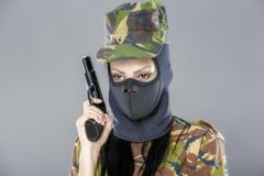 Female soldier in camouflage uniform with weapon isolated on gray background Stock Photos