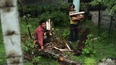 Father and girl collecting fire wood in village, medium shot, shallow DOF Stock Footage