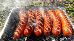 Grilling sausages on disposable BBQ Stock Footage