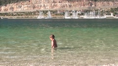 Cute sturdy child stands in the sea- Stock Footage