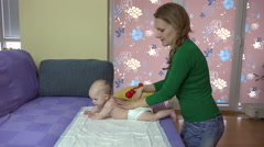Mother make exercise with baby on couch. Baby roll over stomach. 4K Stock Footage