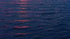 Light waves on the water at night with glare from sunlight Stock Footage