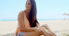 Happy Pretty Woman Sitting at the White Beach Sand Stock Footage