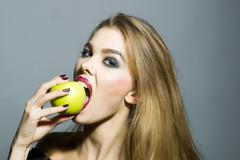 Sexual blonde girl with apple Stock Photos