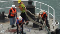 Men secure ship mooring lines over bollard, Singapore Stock Footage