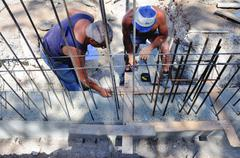 Foreman and worker mark the footprint of a concrete structure in elevation. I - stock photo