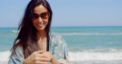 Smiling Pretty Girl at the Beach Wears Sunglasses Stock Footage