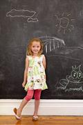 Innocent little girl standing with chalk drawings at home - stock photo