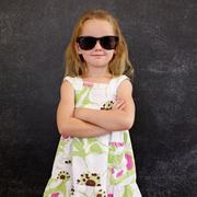 Cute little girl in shades against a black wall Stock Photos