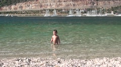 Zoom in child standing in the sea Stock Footage