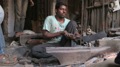 Man shaping a blade with mallet on stone in workshop in Varanasi. Stock Footage