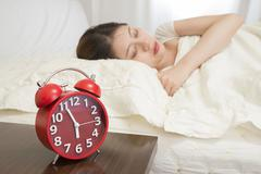 Woman sleeping in bed beside alarm clock - stock photo