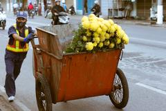 Unidentified Vietnamese man carries a garbage box with flowers. Kuvituskuvat