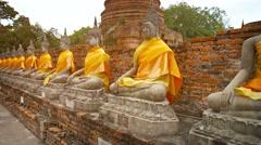 Video UltraHD - Row of stone statues of Buddha dressed in orange fabric at Wa - stock footage