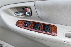 car interior details of door handle with windows controls and adjustments - stock photo