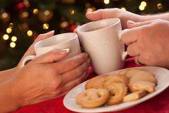 Man and Woman Sharing Hot Chocolate and Cookies in Front of Holiday Lights. Stock Photos