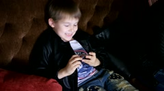 Boy school age play game in smartphone during sitting in cafe with parents Stock Footage