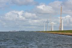 Dutch construction site building wind turbines seen from the sea - stock photo