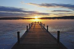 Symmetrical view of jetty on frozen lake, hills in background at sunrise Stock Photos